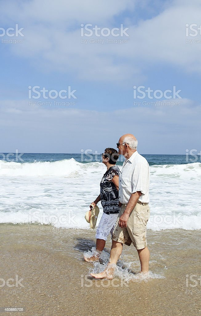 Happy senior couple walking together on a beach royalty-free stock photo