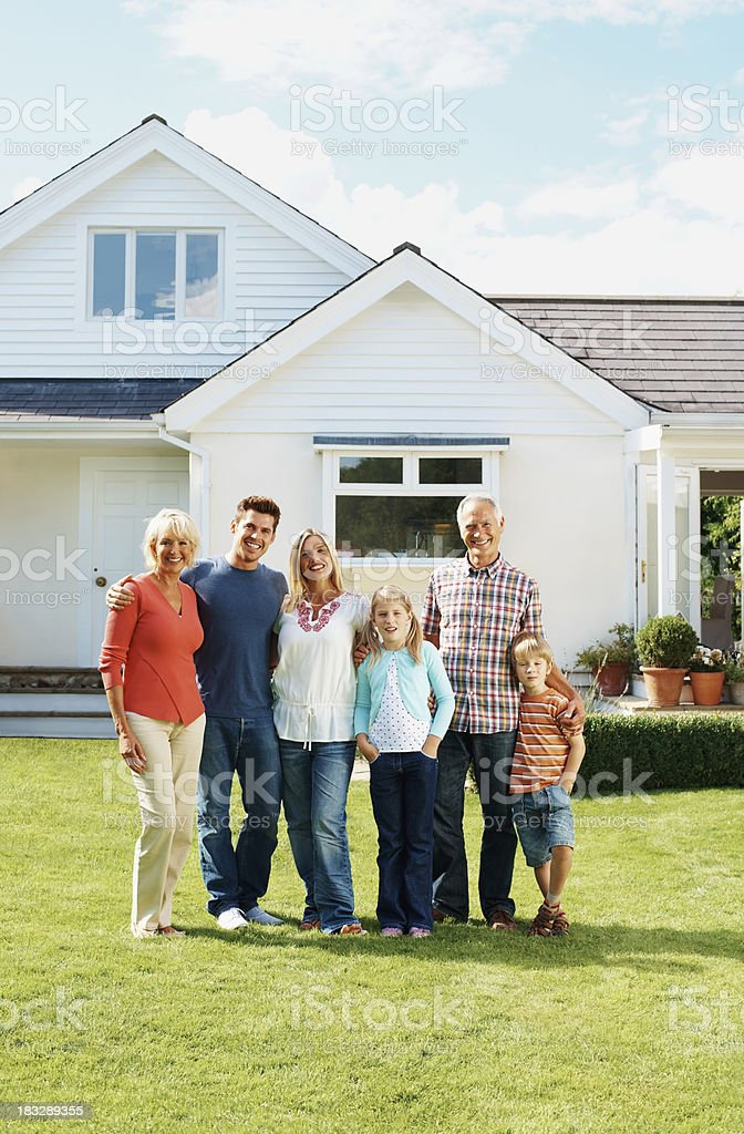 Happy senior couple with family standing in front of house royalty-free stock photo