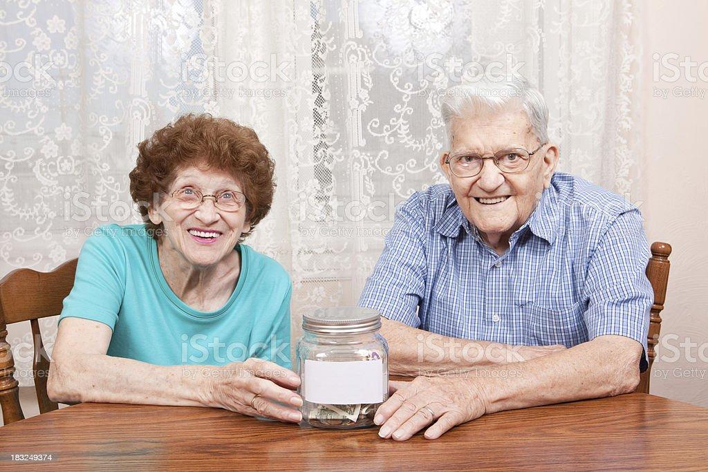 Happy Senior Couple With Money Jar royalty-free stock photo