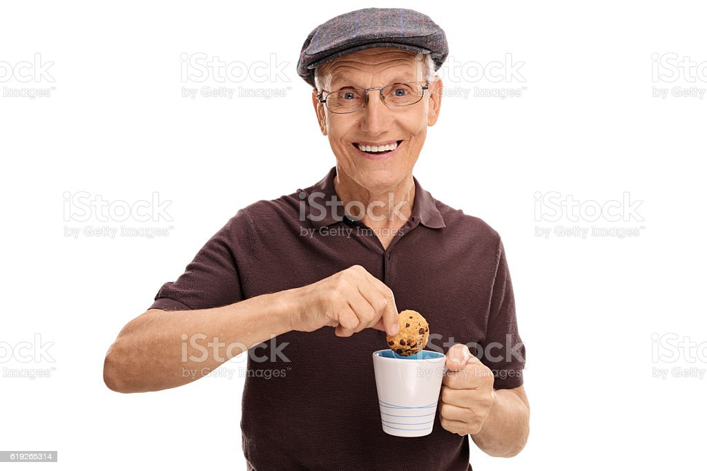 Happy senior dipping a cookie in a cup stock photo