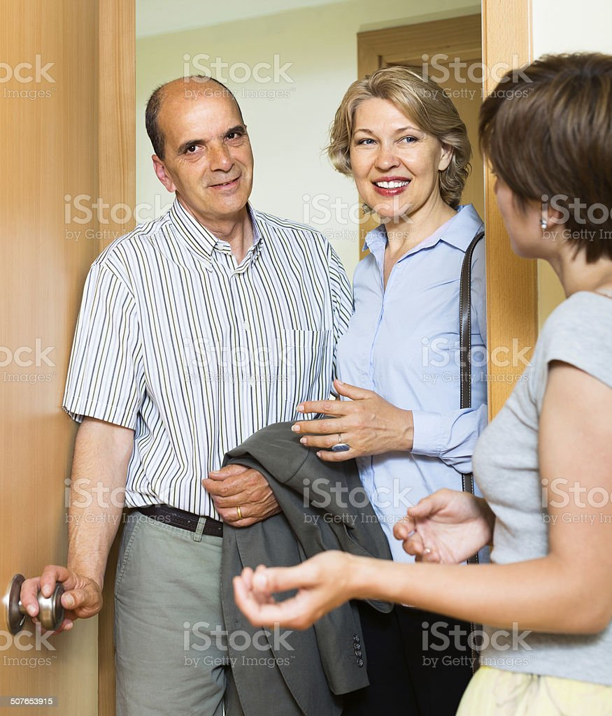 Happy senior family couple visiting daughter stock photo