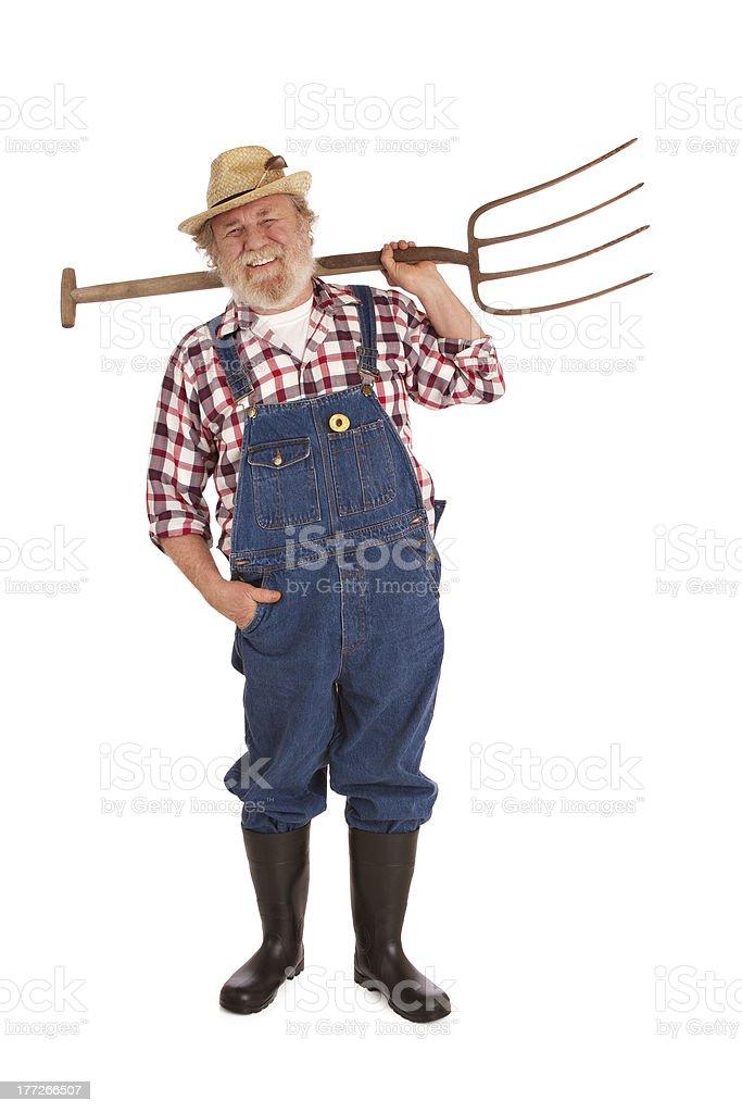 Happy senior farmer lifting hay fork up stock photo