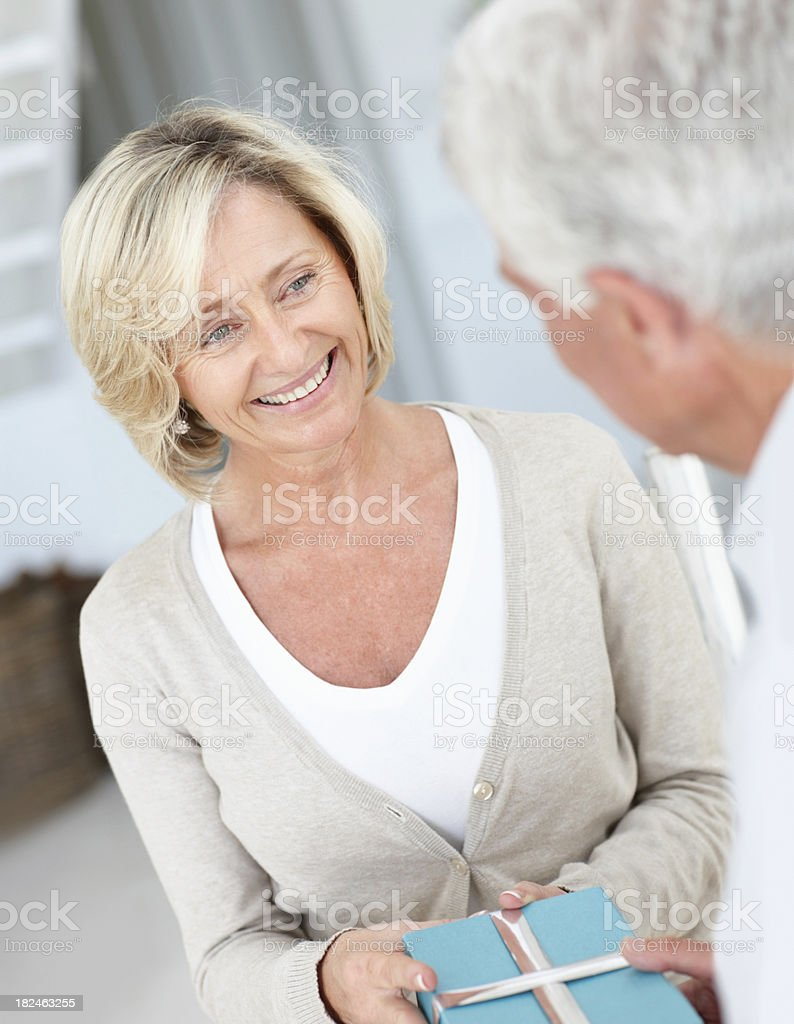 Happy senior female being greeted with a gift by husband royalty-free stock photo