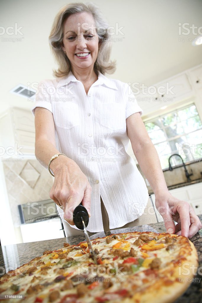 Happy Senior Homemaker Cutting Her Large Fresh Pizza royalty-free stock photo