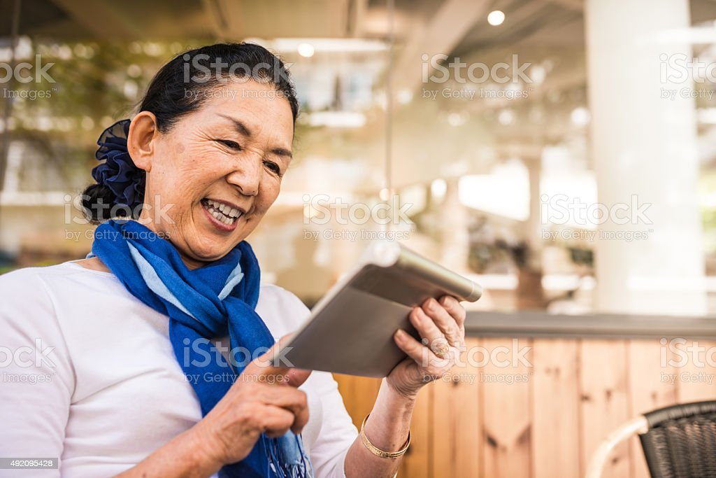 Happy Senior Japanese women using touch pad stock photo