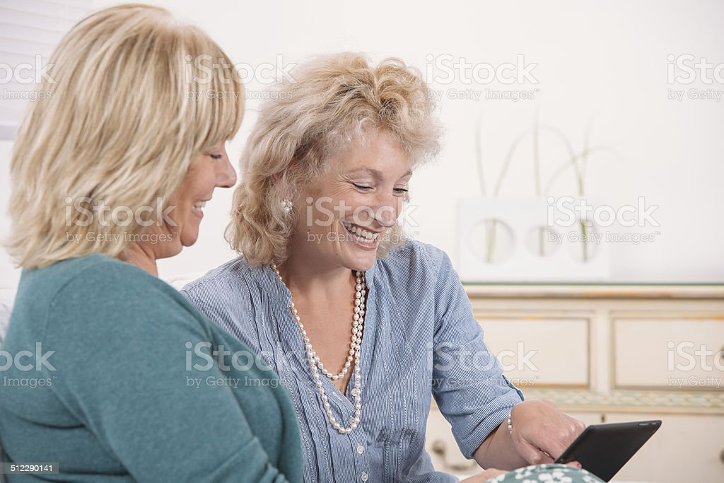 Happy Senior Ladies Using A Digital Tablet stock photo