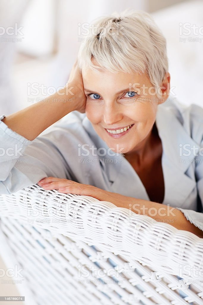 Happy senior lady on wicker chair royalty-free stock photo