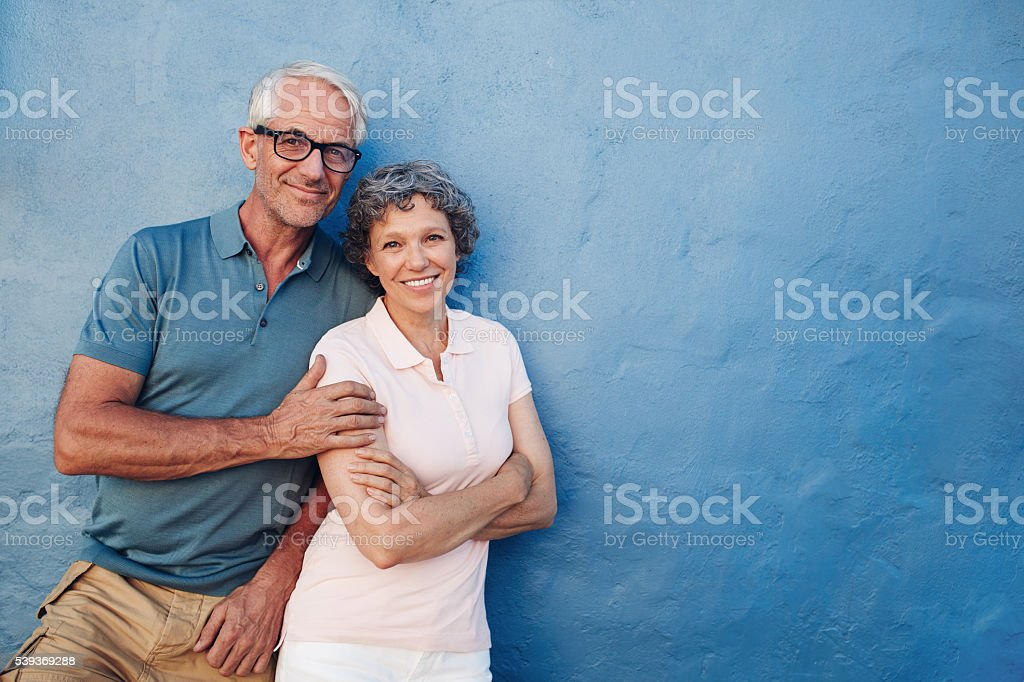 Portrait of happy senior man and woman together against blue...