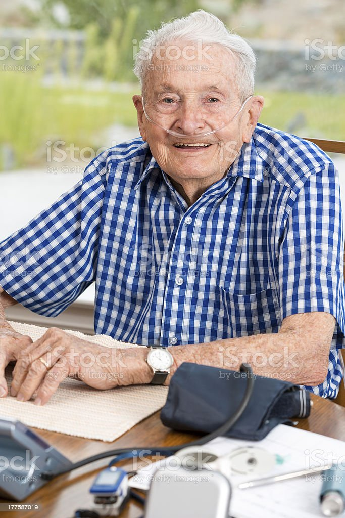 Happy senior man at the table filled with medical equipment stock photo