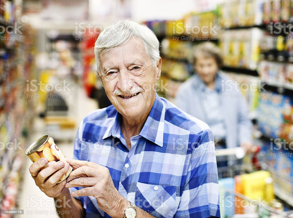 Happy senior man checks can label in supermarket stock photo