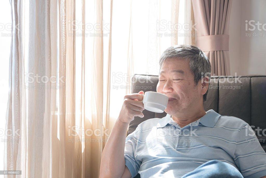 Happy senior man drinking stock photo