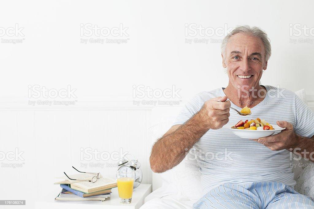 Happy senior man eating breakfest stock photo
