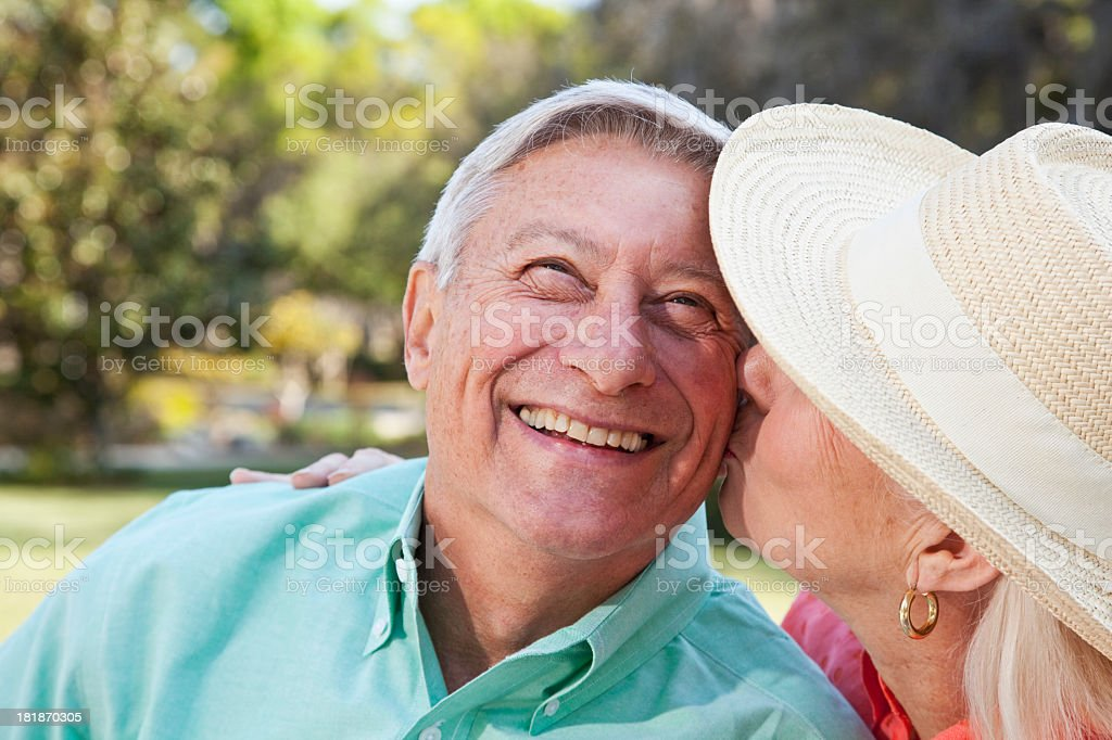 Happy senior man getting kiss from wife royalty-free stock photo