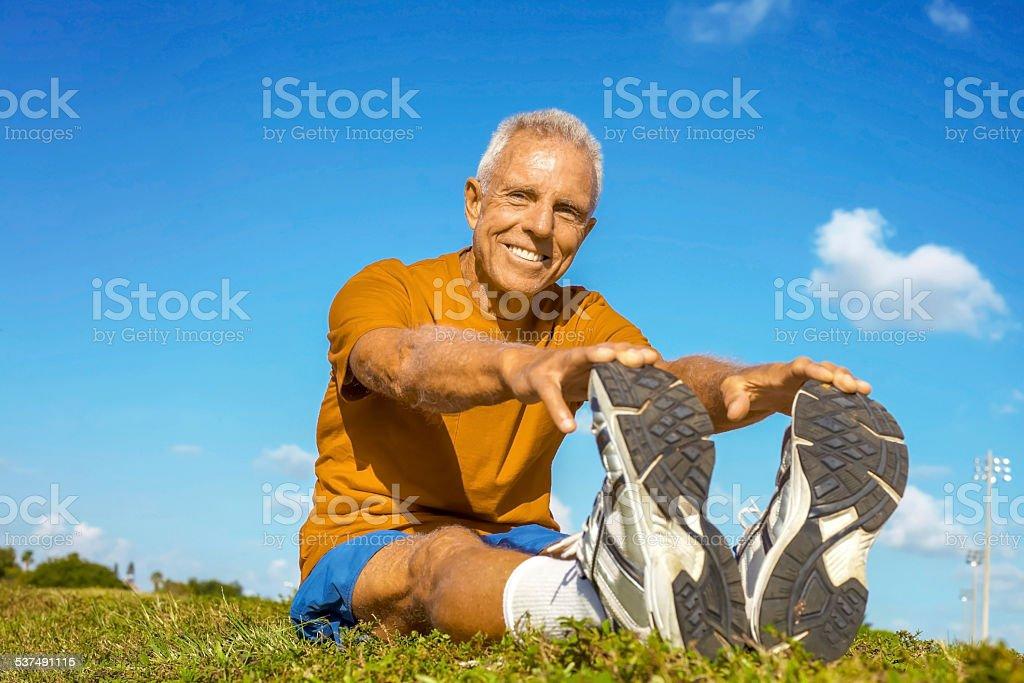 Happy Senior Man In Sportswear Stretching On Field stock photo