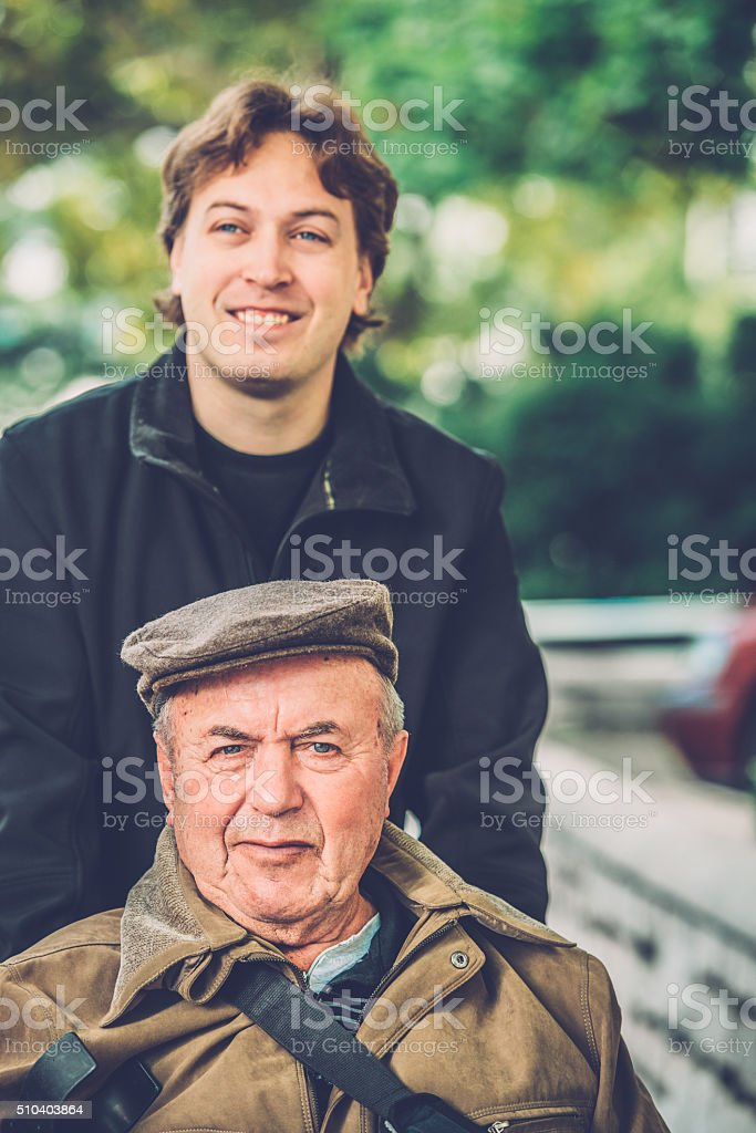 Happy Senior Man in Wheelchair and Grandson Outdoors, Europe stock photo