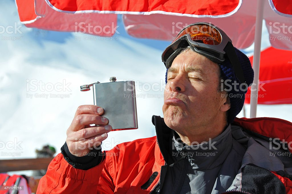 Happy senior man outdoors drinking out hip flask during wintersport royalty-free stock photo