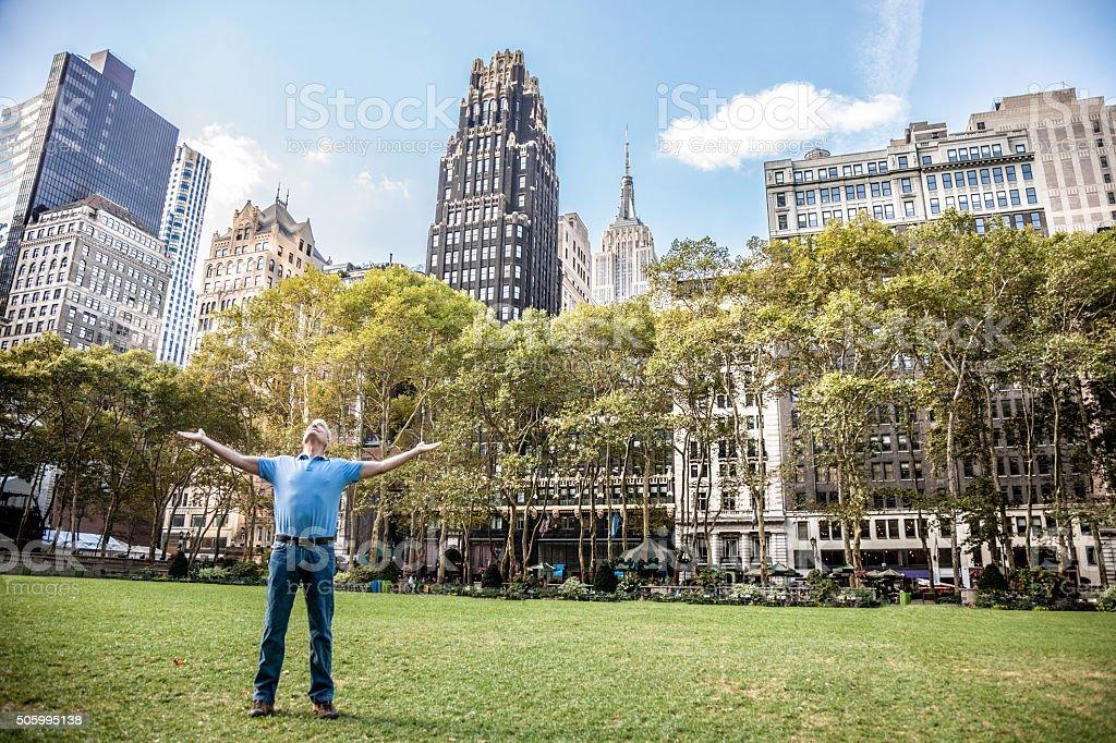 Happy senior man raising arms in the city stock photo