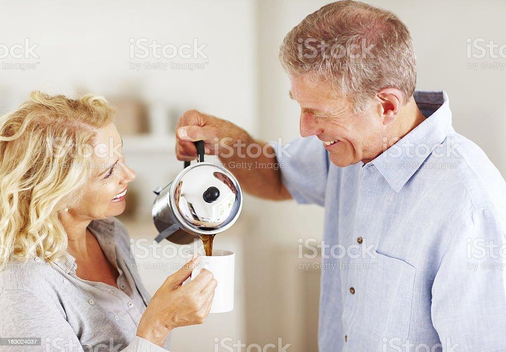 Happy senior man serving tea to mature woman at home royalty-free stock photo