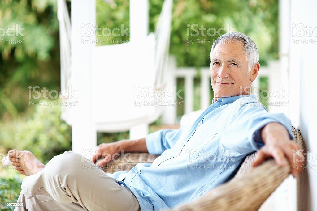 Happy senior man sitting on wicker chair at veranda stock photo