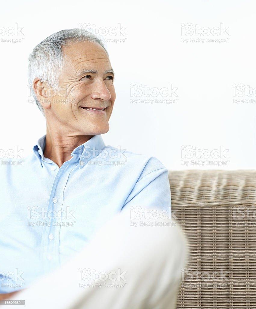 Happy senior man sitting on wicker chair smiling against white stock photo
