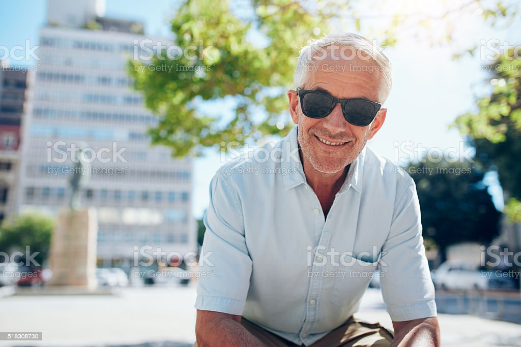 Happy senior man sitting outdoors in the city stock photo