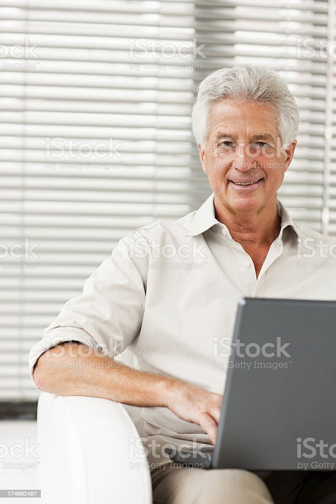 Happy senior man sitting with laptop royalty-free stock photo