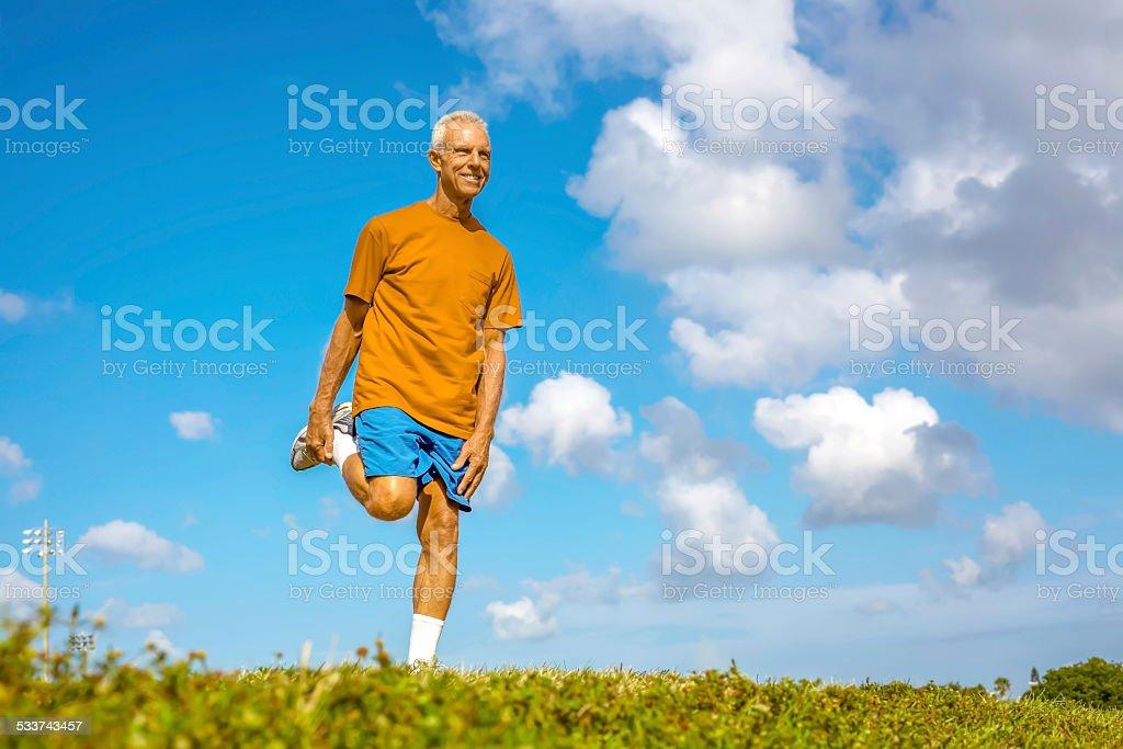 Happy Senior Man Stretching Leg On Meadow stock photo