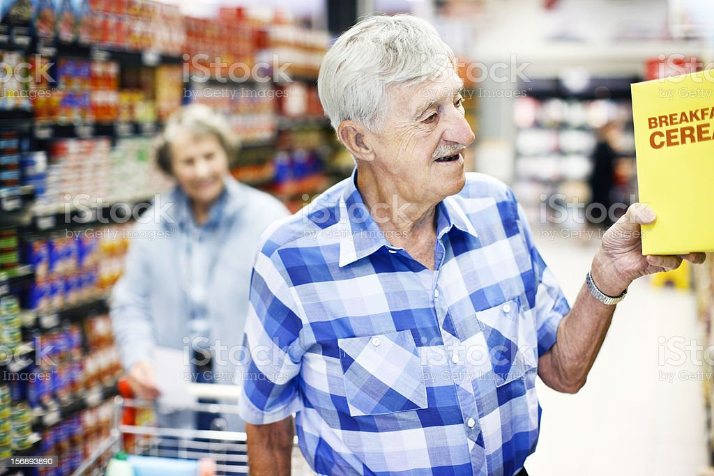 Happy senior man takes cereal from supermarket shelf stock photo