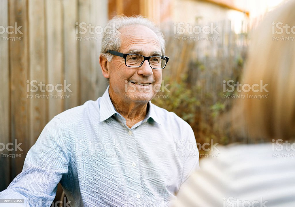 Happy senior man talking with woman in backyard stock photo