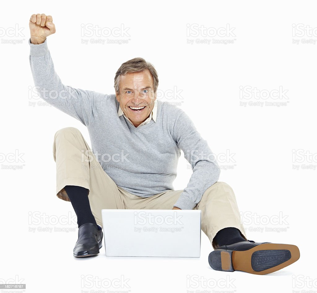 Happy senior man using a laptop while sitting on white royalty-free stock photo