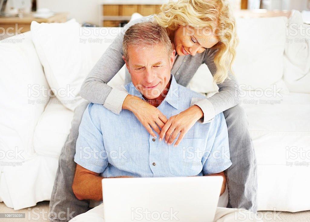 Happy senior man using laptop while woman embraces him royalty-free stock photo