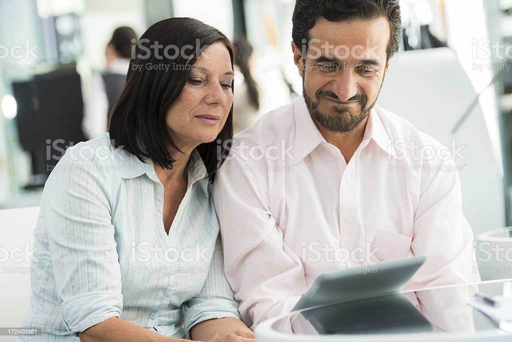 Happy senior man with his wife holding a digital tablet royalty-free stock photo