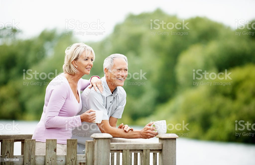 Happy senior man with mature woman holding cup of tea stock photo