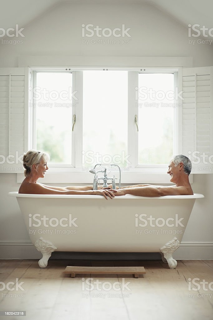 Happy senior man with mature woman in a bathtub stock photo