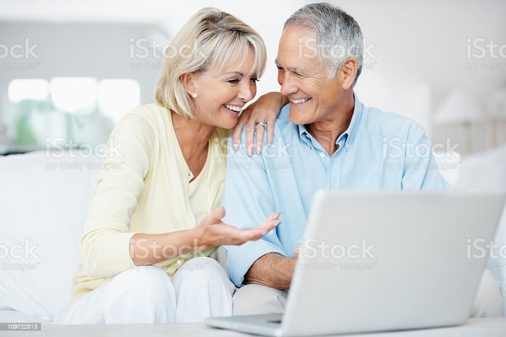 Happy senior man with surprised woman working on a laptop royalty-free stock photo