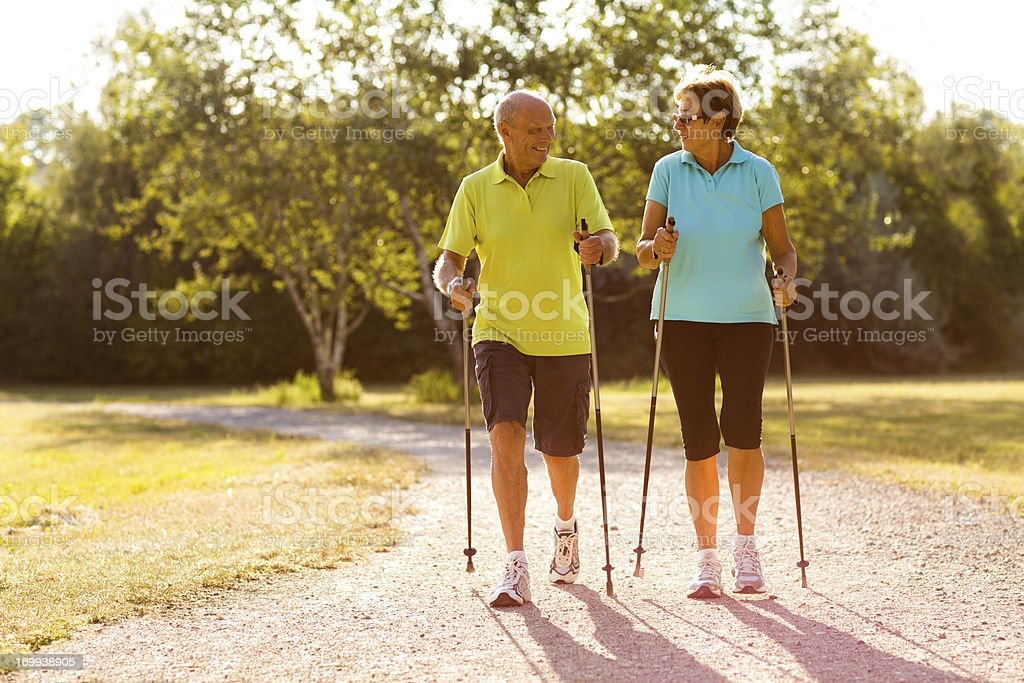 happy senior nordic walking couple stock photo