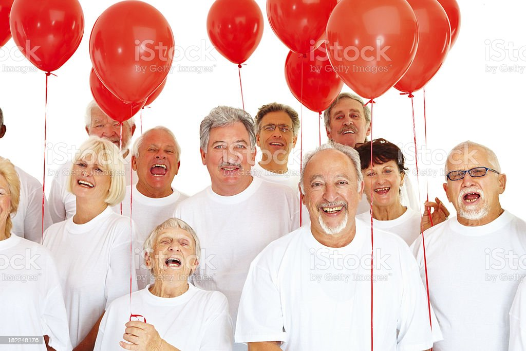 Happy senior people holding red balloon royalty-free stock photo