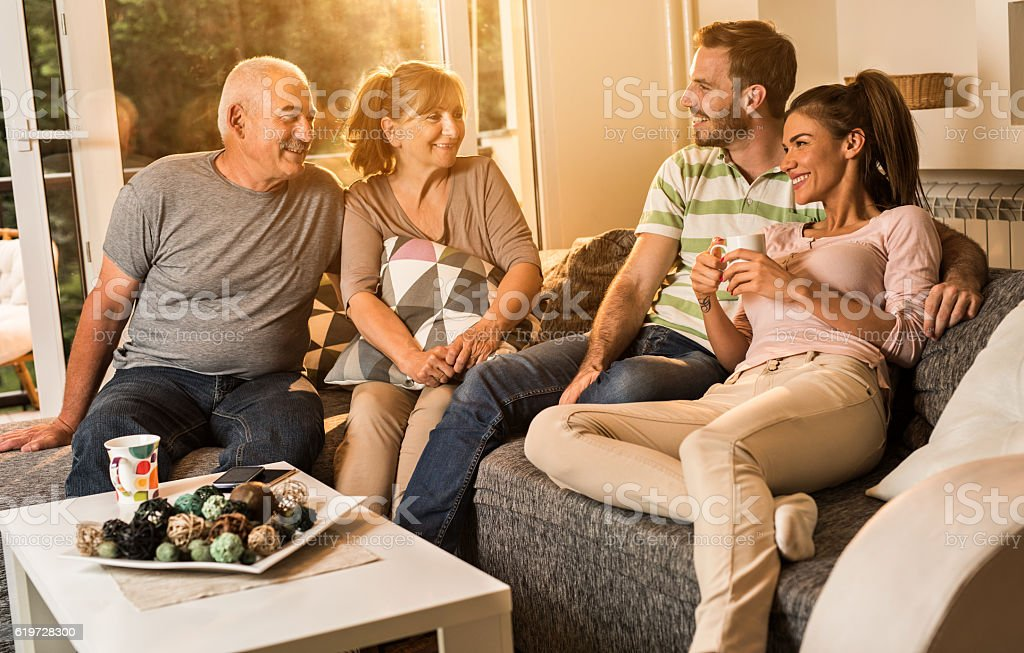 Happy senior people talking to young couple at home. stock photo