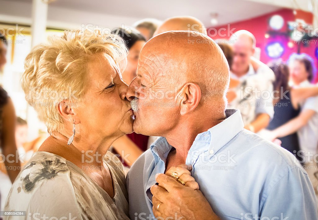 Happy senior retired couple having fun on dancing kiss stock photo