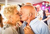 Happy senior retired couple having fun on dancing kiss
