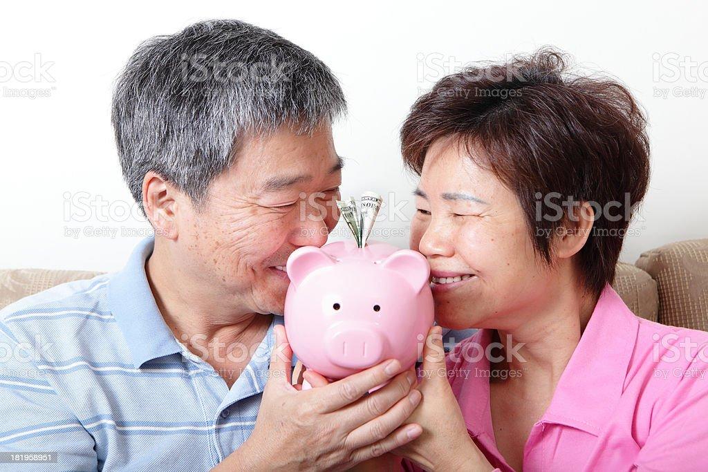 Happy senior retired couple kiss piggy bank royalty-free stock photo