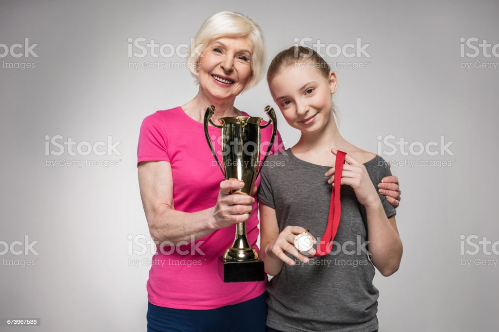 Happy senior sportswoman and girl holding trophy and medal isolated on grey stock photo