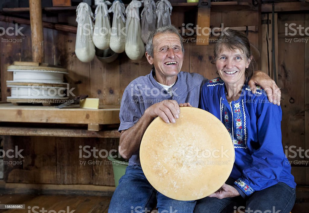 Happy Senior Swiss Couple Holding A Loaf Of Selfmade Cheese royalty-free stock photo