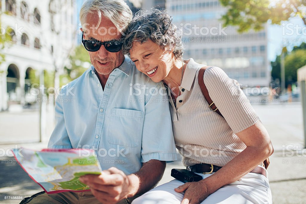 Happy senior tourists looking at a city map stock photo