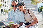 Happy senior tourists looking at a city map