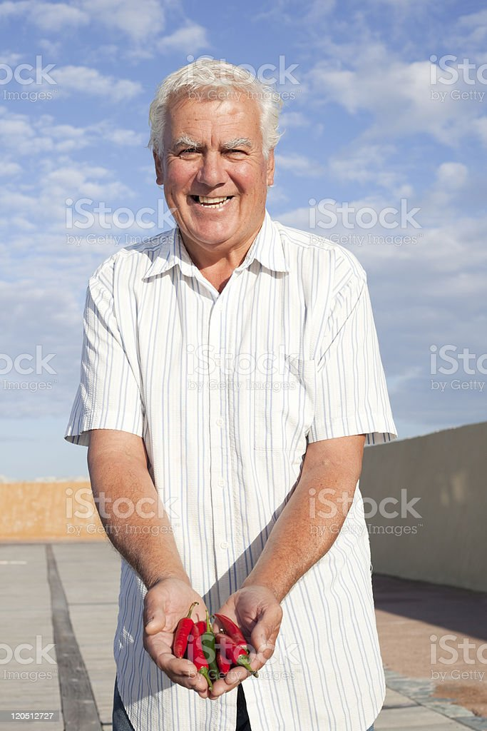 Happy senior with chilipepper. royalty-free stock photo
