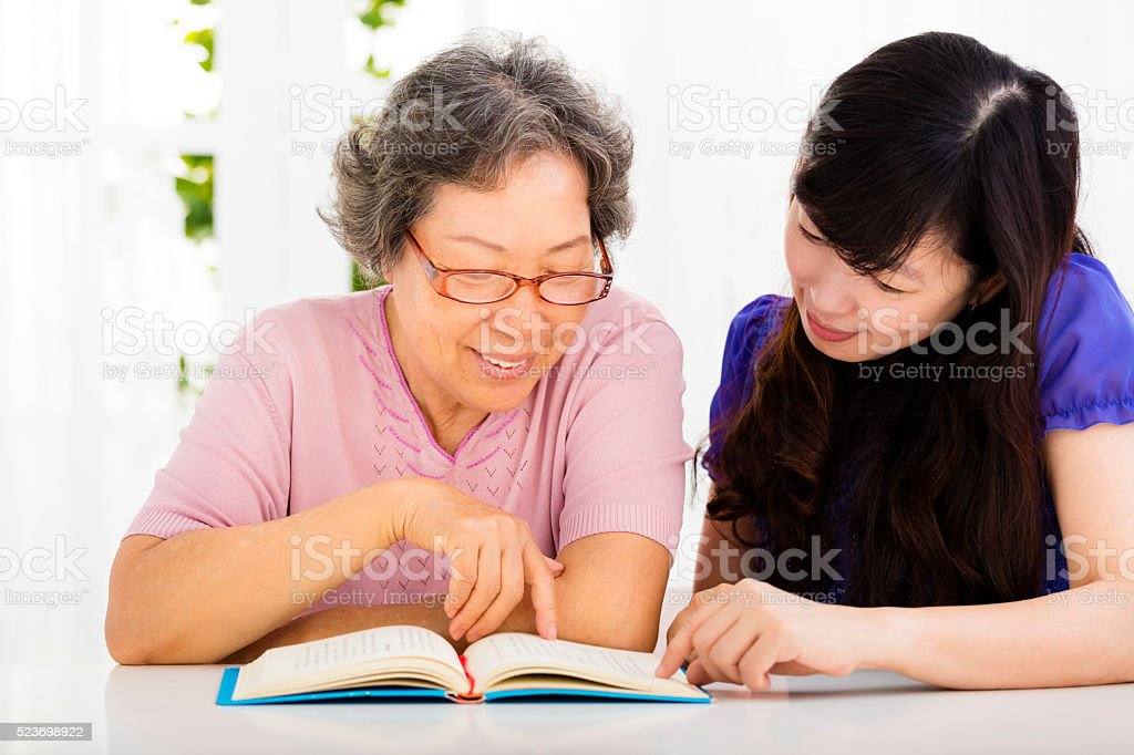 happy senior woman and  daughter  reading a book stock photo