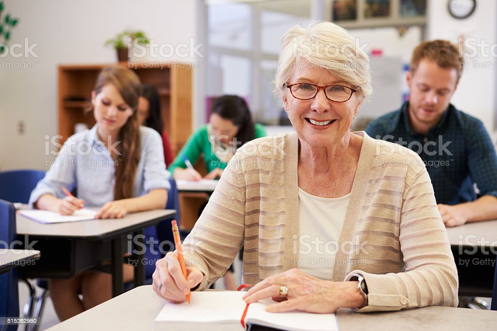 Happy senior woman at an adult education class looking stock photo