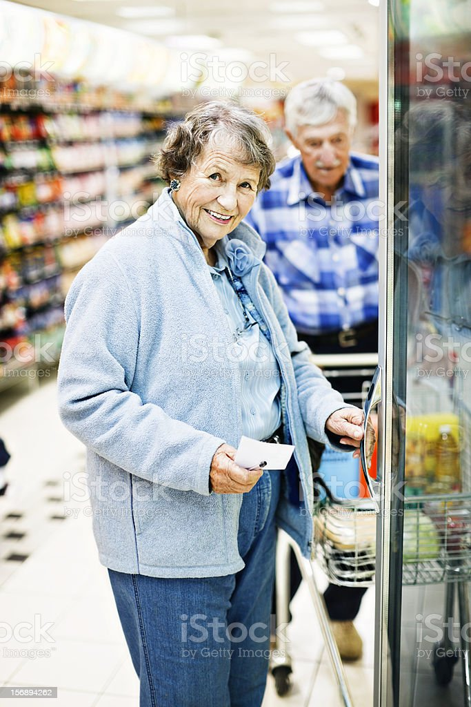 Happy senior woman by supermarket fridge, her husband in background stock photo
