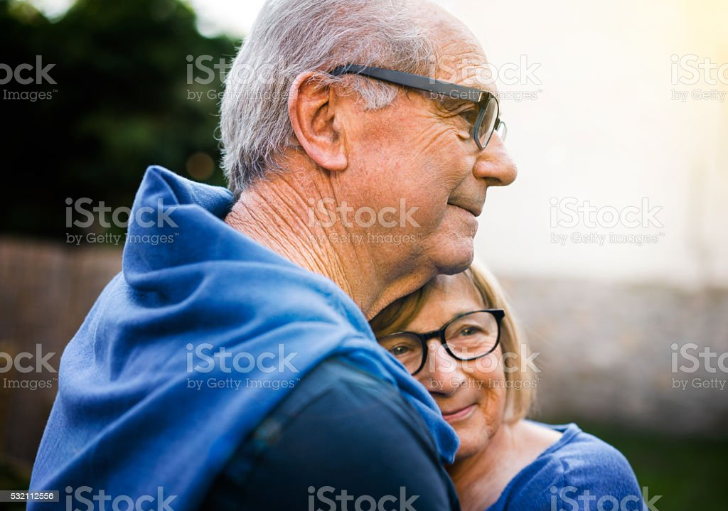 Happy senior woman embracing man in backyard stock photo